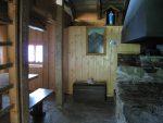 L'intérieur, un peu sombre, la grande cheminée et les marches pour monter aux couchettes