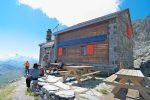 La cabane de Valsorey et la gardienne devant en bleu, de dos