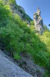 On traverse un pierrier avec en face le Rocher de la Poupée. Le couloir de montée est à gauche de ce rocher.